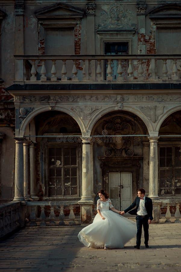 Het huwelijksportret van gemiddelde lengte van het dansende jonggehuwdepaar op het balkon van het oude kasteel stock afbeeldingen