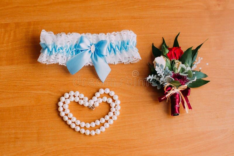 Het huwelijkstoebehoren van de bruid, witte kouseband met blauw lint, armband van parels en leuk weinig boutonniere preparing stock afbeelding