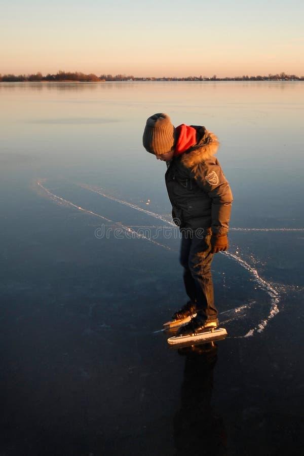 Het ijs van de jongen het schaatsen stock foto