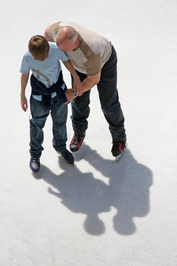 Het ijs van de vader en van de zoon het schaatsen royalty-vrije stock afbeeldingen
