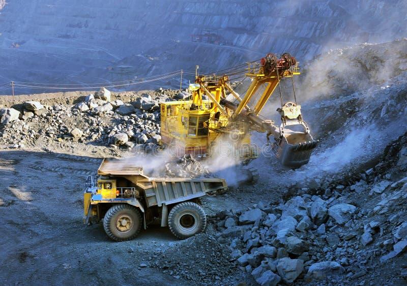 Het ijzererts van de graafwerktuiglading in zware stortplaatsvrachtwagens stock foto's