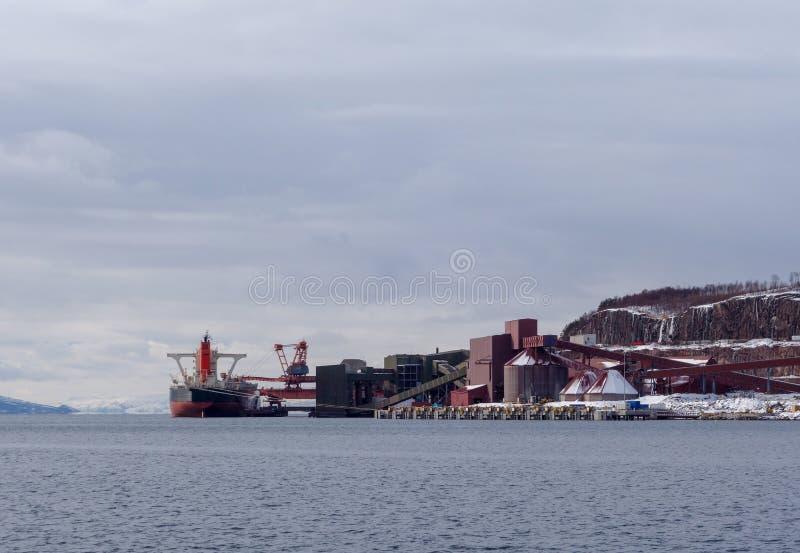 Het ijzererts van de vrachtschiplading bij de Haven van Narvik in noordelijk Noorwegen op een de winterdag stock foto