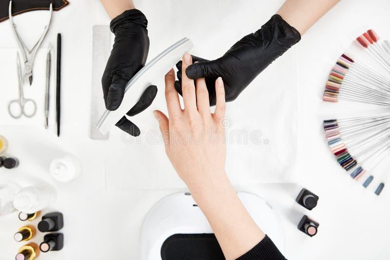 Het indienen van spijkertechnologie spijkers met nagelvijl Professionele manicurehulpmiddelen royalty-vrije stock afbeeldingen