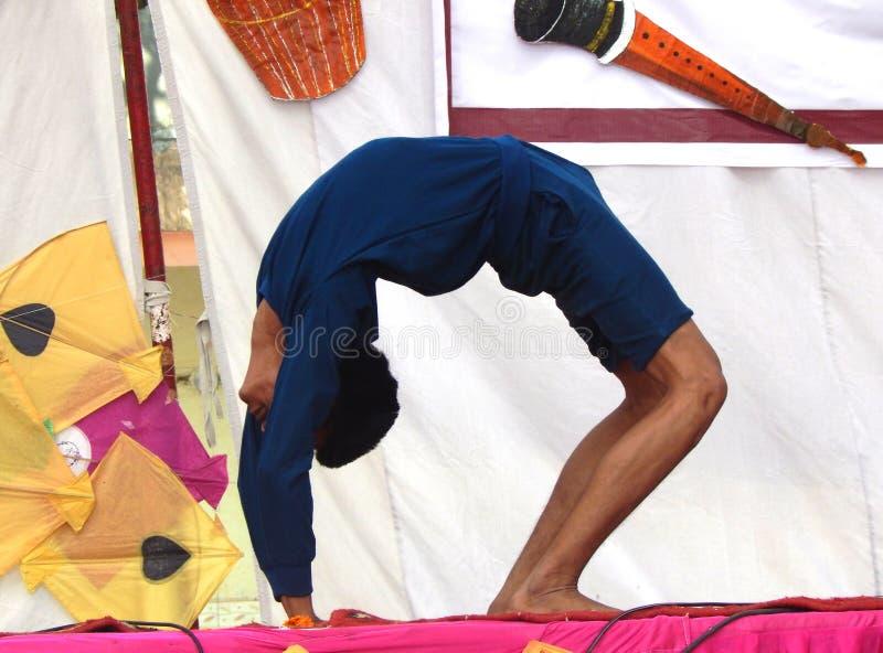 Het Indische jongen presteren yogaasan op stadium stock foto
