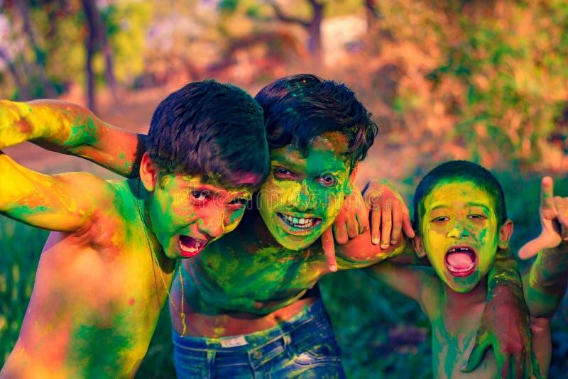 Het Indische kind spelen met de kleur in holifestival stock foto's