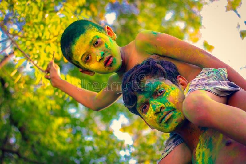 Het Indische kind spelen met de kleur in holifestival stock fotografie