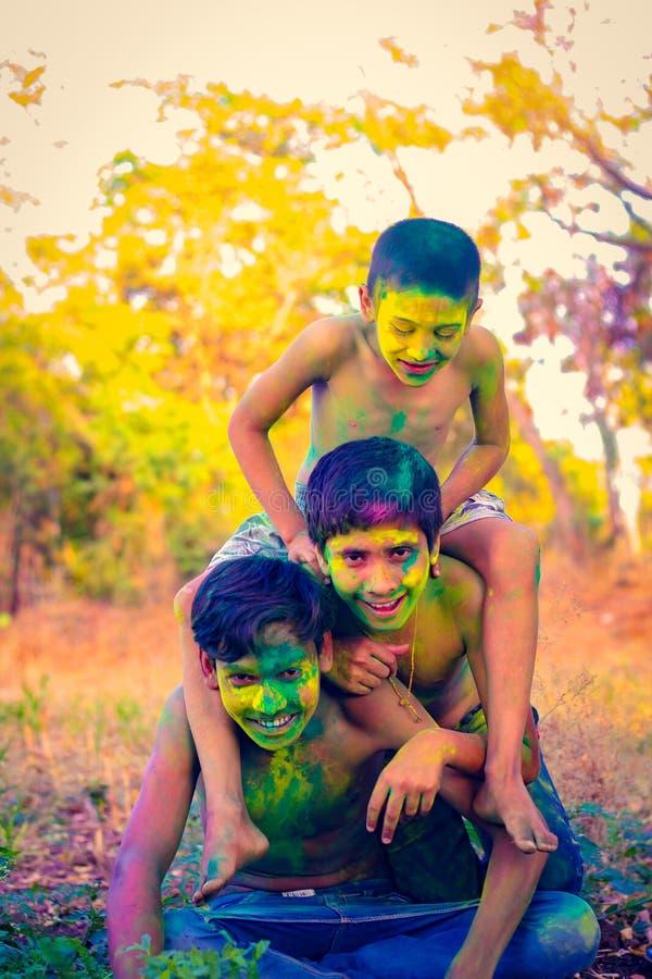 Het Indische kind spelen met de kleur in holifestival stock afbeelding