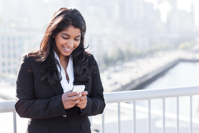 Het Indische onderneemster texting op de telefoon stock foto's
