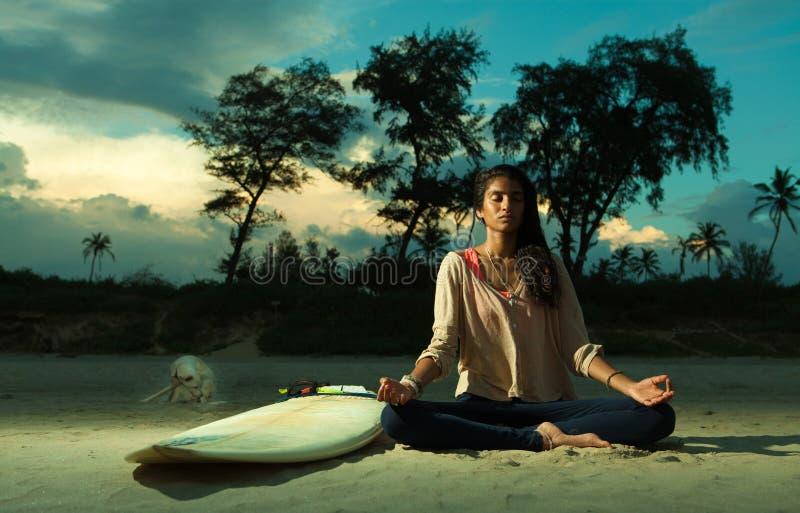 Het Indische surfermeisje mediteren in lotusbloem stelt op het strand bij zonsondergang naast surfplank royalty-vrije stock foto's