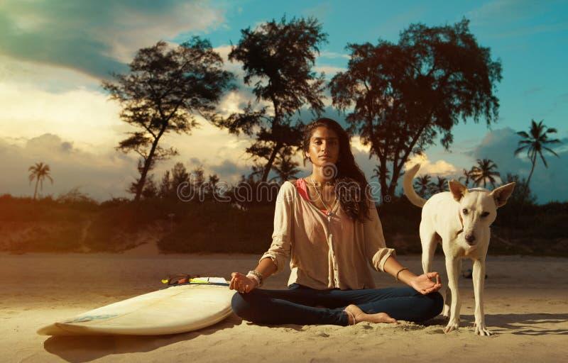 Het Indische surfermeisje mediteren in lotusbloem stelt op het strand bij zonsondergang naast surfplank stock foto