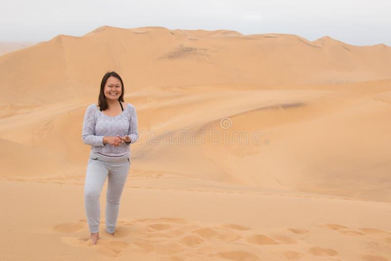 Het Indonesische meisje stellen op Duin 7 in Walvis-Baai, Namibië royalty-vrije stock foto's
