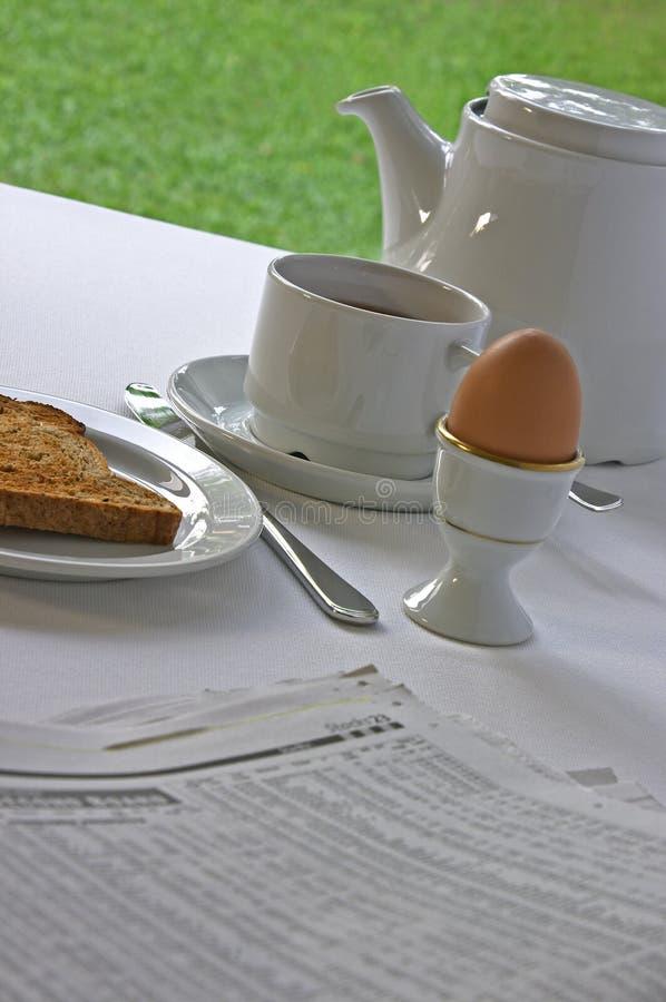 Het inhalen op BedrijfsNieuws bij Ontbijt stock afbeelding
