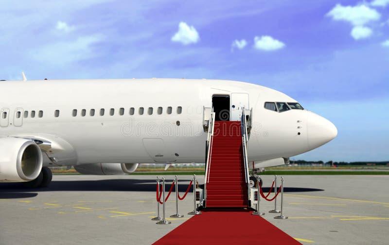 Het inschepen van commercieel vliegtuig met rode tapijtpresentatie stock afbeelding