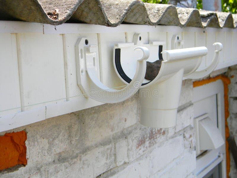 Het installeren van de plastic houder van de dakgoot voor dowspoutrioolbuis Het plastic dak guttering, regen het guttering & drai royalty-vrije stock foto's