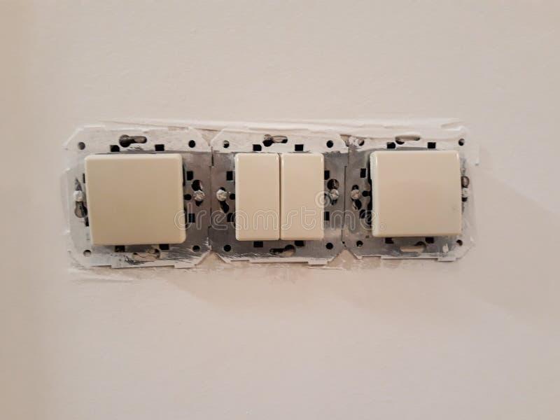het installeren van een elektroschakelaar in een huis onder vernieuwing op de muur stock afbeeldingen