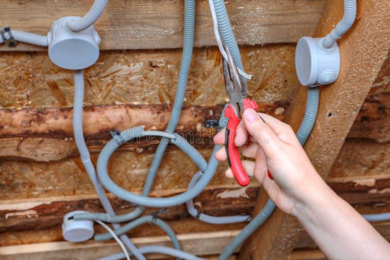 Het installeren van plafond lichte bedrading, elektricien mounter hand met p stock afbeeldingen