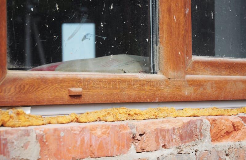 Het installeren van plastic venster in baksteenhuis met waterdicht makend kanonschuim stock foto