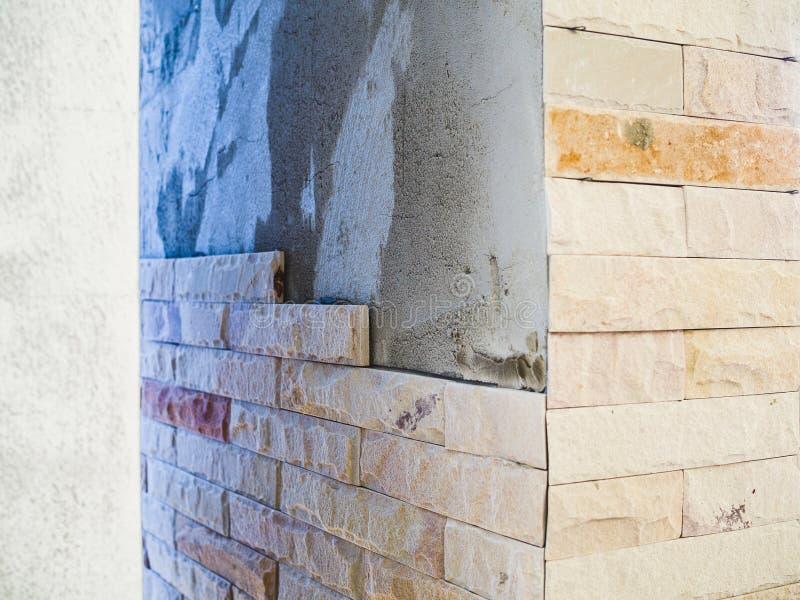 Het installeren van zandsteen decoratieve tegels op het pijlershuis royalty-vrije stock foto's