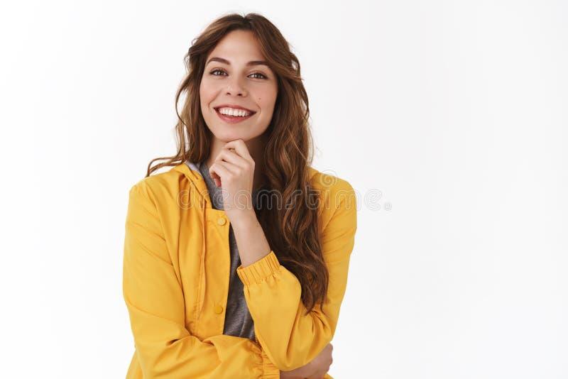 Het interessante idee denkt over het Het geamuseerde enthousiaste gelukkige knappe Europese vrouwen modieuze gele jasje glimlache stock foto's