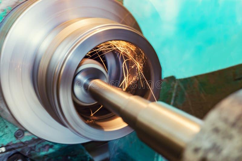 Het interne malen van een cilindrisch deel met een schurend wiel op een machine, vonken vliegt in verschillende richtingen Metaal stock foto