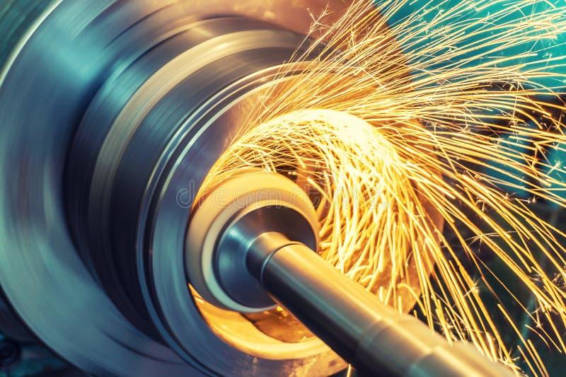 Het interne malen van een cilindrisch deel met een schurend wiel op een machine, vonken vliegt in verschillende richtingen Metaal stock fotografie