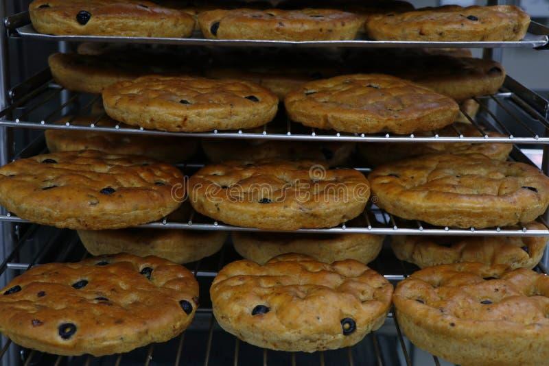Het Italiaanse brood van olijffocaccia in bakseldienbladen stock foto's