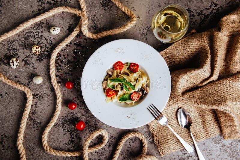 Het Italiaanse diner van stijldeegwaren Spaghetti met tomaat en basilicum in plaat op houten raad royalty-vrije stock afbeeldingen
