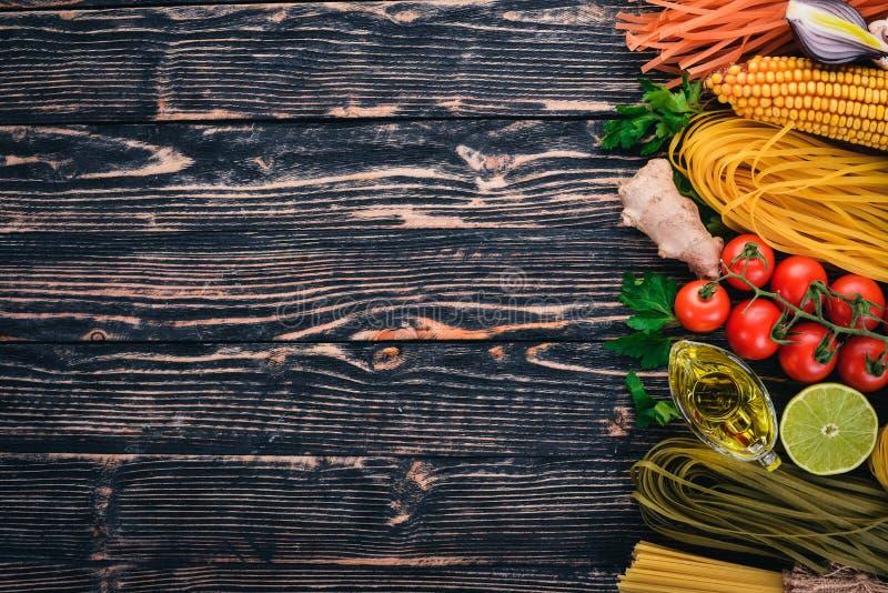 Het Italiaanse koken, verse groenten en kruiden Reeks van deegwaren, noedels, spaghetti Op een donkere houten achtergrond royalty-vrije stock foto's