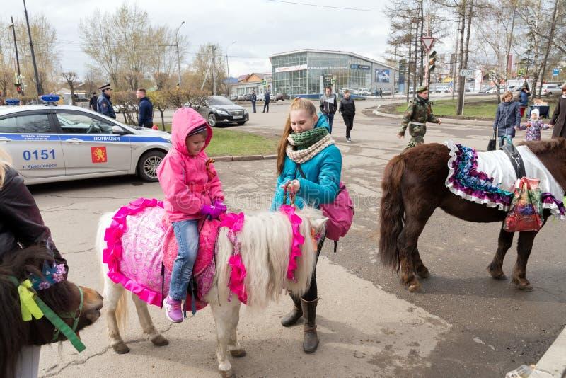 Het Ittlemeisje zit op een poney, bevindt een meisje zich naast haar, tegen de achtergrond van een politiewagen stock afbeelding