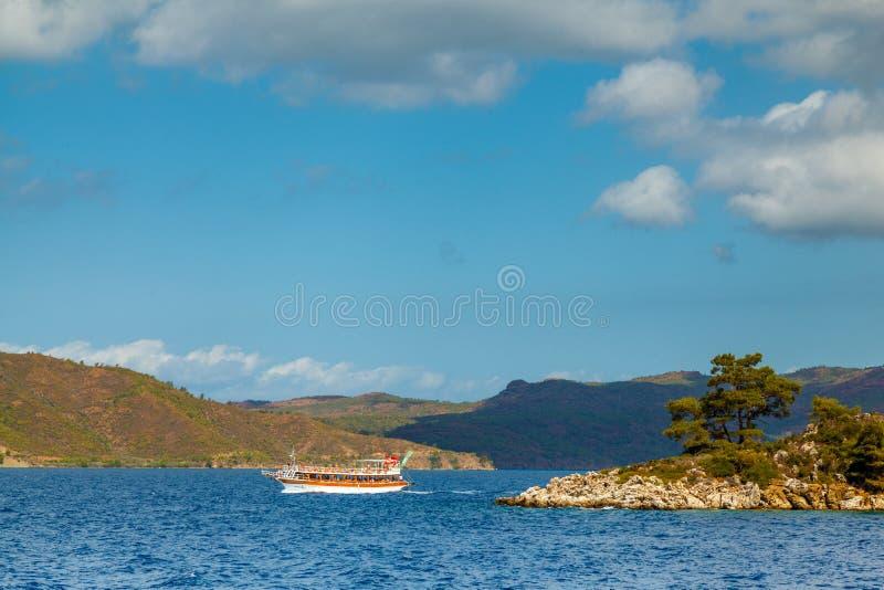 Het jacht drijft nabijgelegen rotsachtige kust met bomen in Aegea royalty-vrije stock foto
