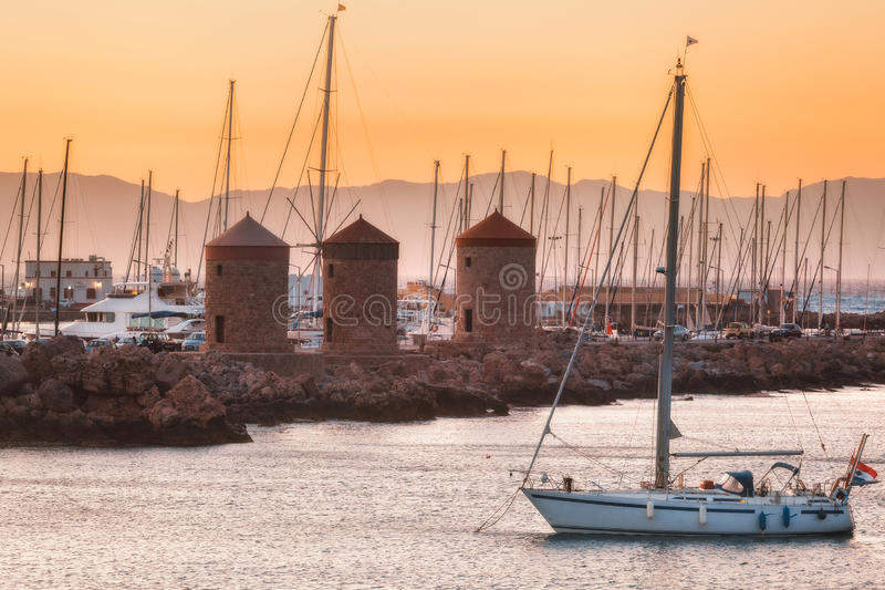 Het jacht op de achtergrond van de molens in de Mediterrane haven Mandraki Het eiland van Rhodos Griekenland royalty-vrije stock fotografie