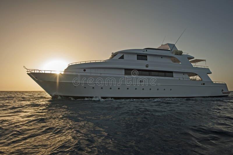 Het jacht van de luxemotor op zee in zonsondergang royalty-vrije stock fotografie