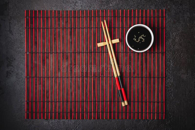 Het Japanse lijst plaatsen Bamboeeetstokjes en sojasauskom op gestreepte mat royalty-vrije stock foto
