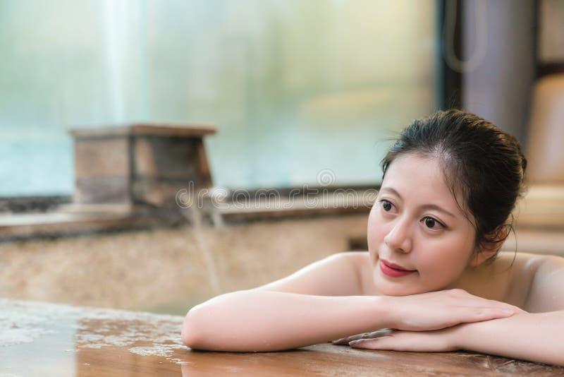 Het Japanse meisje neemt een rust liggend op poolside stock foto