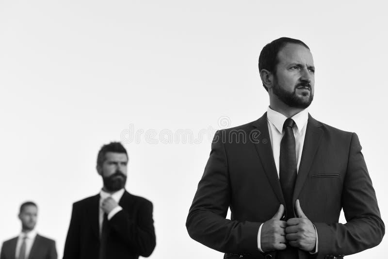 Het jasje van zakenliedenaanrakingen De managers dragen slimme kostuums en banden royalty-vrije stock afbeeldingen