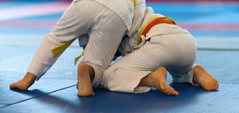 Het jong geitjejudo, kinderen martial kunst in de zaalconcurrentie op judoschool stock fotografie