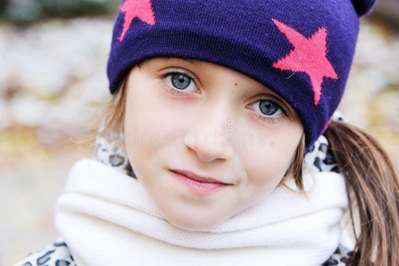 Het jong geitjemeisje heeft pret in tuin met eerste sneeuw royalty-vrije stock foto