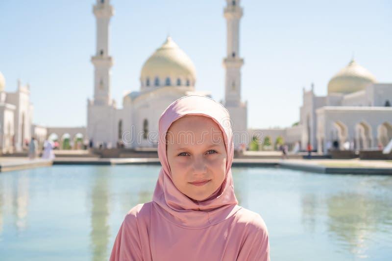 Het jong geitjemeisje in roze hijab zit naast een witte moskee Op de straat Dichtbij het meer stock afbeeldingen