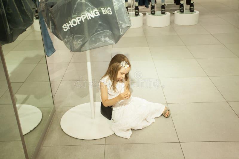 Het jong geitjemeisje wacht mama in winkel De kinderen vermoeien na het winkelen stock foto's