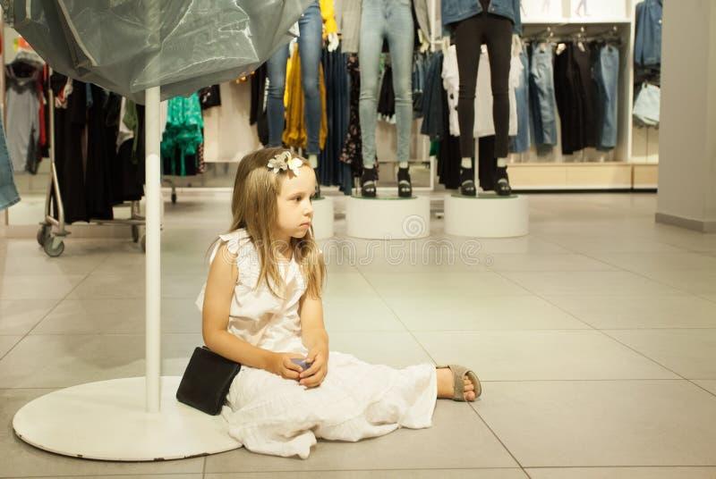 Het jong geitjemeisje wacht mama in winkel De kinderen vermoeien na het winkelen royalty-vrije stock fotografie