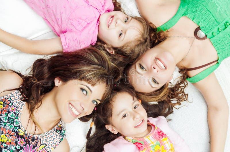 Het jonge aanbiddelijke Spaanse meisjes en moeders liggen royalty-vrije stock foto