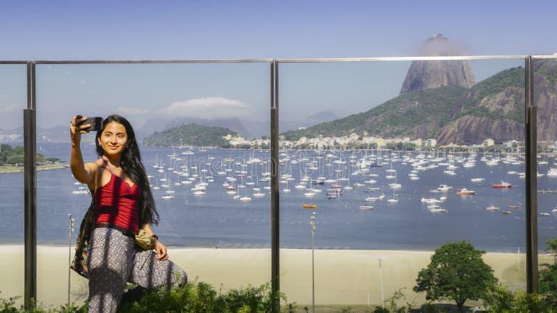 Het jonge aantrekkelijke Braziliaanse meisje neemt een selfie die Sugarloaf-Berg in Rio de Janeiro, Brazilië overzien royalty-vrije stock afbeelding