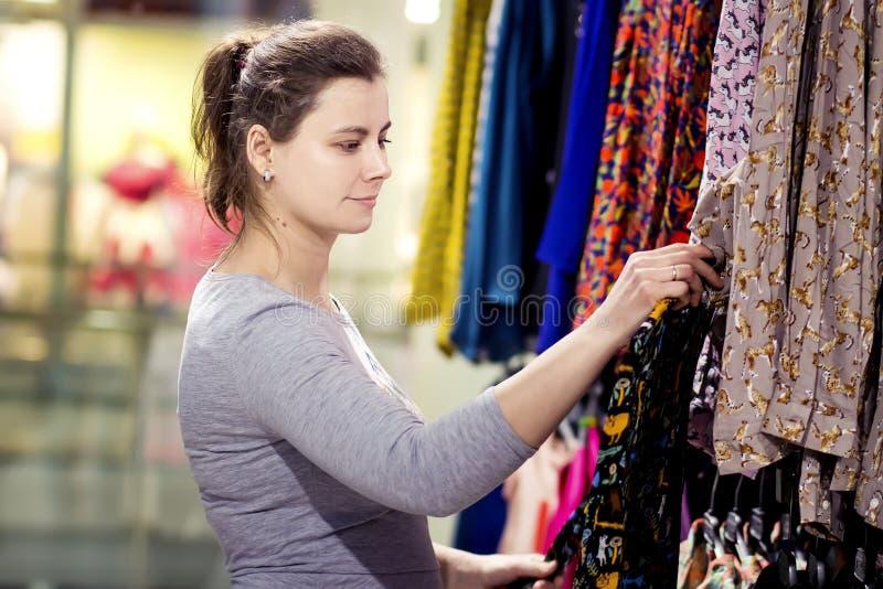 Het jonge aantrekkelijke donkerbruine meisje kiest kleren in in boutique de vrouw koopt nieuwe kleren Shopaholic in de opslag stock afbeelding