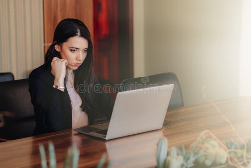 Het jonge aantrekkelijke emotionele meisje in zaken-stijl kleedt het zitten bij een bureau op laptop en telefoon in het bureau of royalty-vrije stock foto's