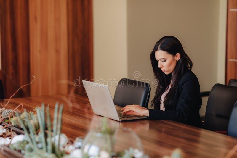 Het jonge aantrekkelijke emotionele meisje in zaken-stijl kleedt het zitten bij een bureau op laptop en telefoon in het bureau of royalty-vrije stock afbeelding