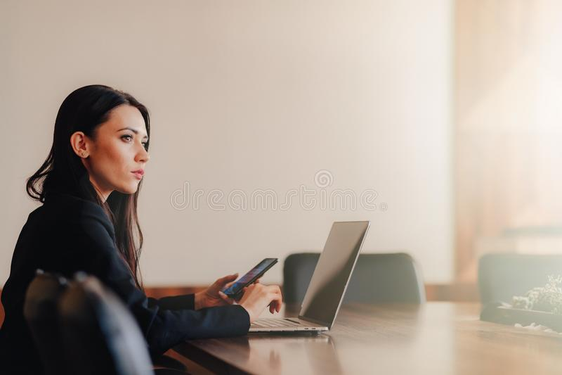 Het jonge aantrekkelijke emotionele meisje in zaken-stijl kleedt het zitten bij een bureau op laptop en telefoon in het bureau of stock fotografie
