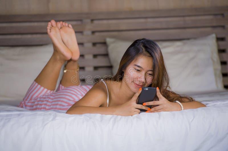 Het jonge aantrekkelijke en gelukkige tienervrouw ontspannen liggen en vrolijk glimlachen in bed gebruikend de sociale media van  royalty-vrije stock foto