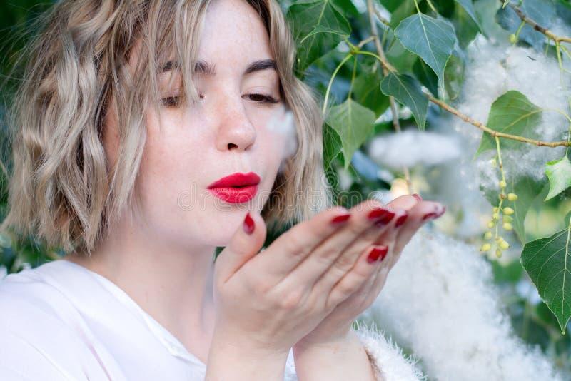 Het jonge aantrekkelijke freckled meisje blaast polaire pluis, rode lippen royalty-vrije stock fotografie