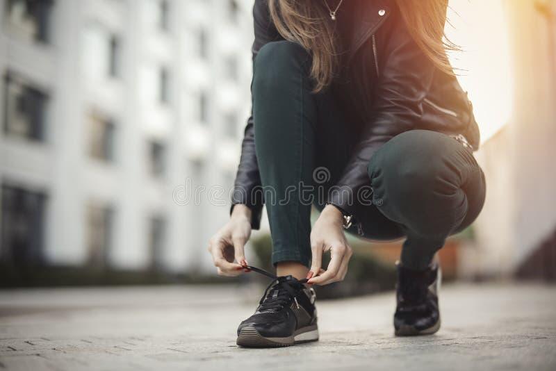 Het jonge aantrekkelijke meisje bindt schoenveters stock foto