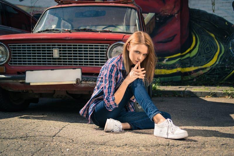 Het jonge aantrekkelijke model zit dichtbij de retro auto royalty-vrije stock fotografie
